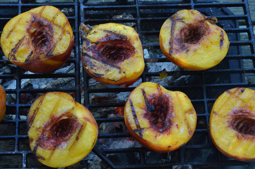 Peach halves grilling on top of a small tabletop Hibachi grill on picnic table outdoors Arrangement Choice Close-up Displayed Extreme Close Up Freshness Fruit Gourmet Grilled Peaches Grilling Group Of Objects Healthy Eating Healthy Food Indulgence No People Peach Halves Peaches Picnic Ready-to-eat Temptation Variation Variety Yellow