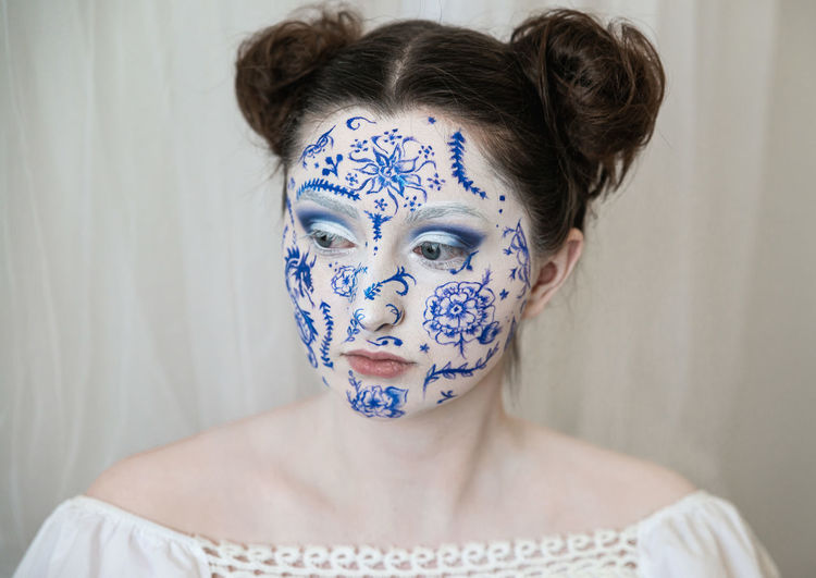 Woman with painted face looking away against curtain at home