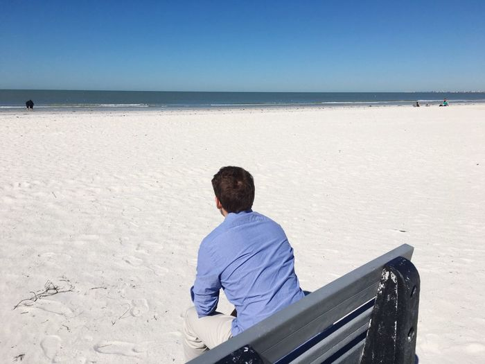 Man sitting on beach at beach against clear sky