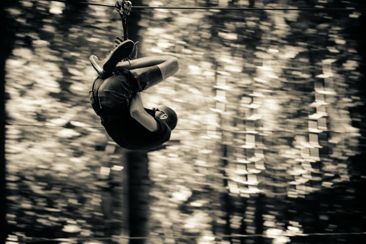 Low Angle View Of Man Zip Lining Against Trees In Forest
