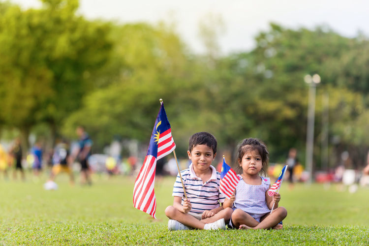 Boy and son flag on grass