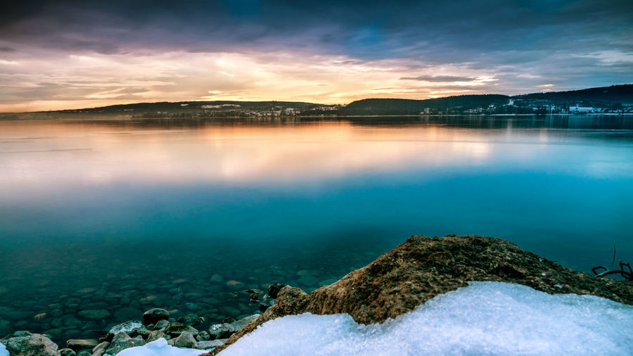 Beautiful sunrise on lake constance with stones on the lake shore and snow