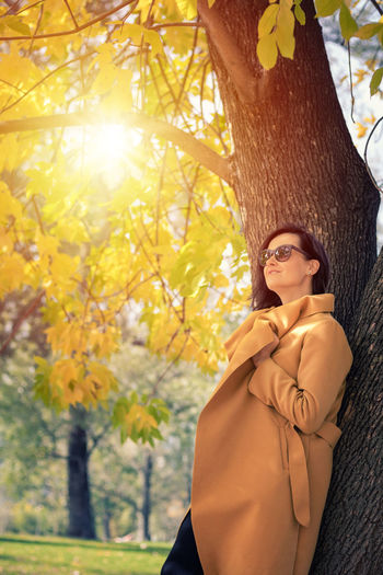 Autumn Fashion Females Lifestyle Sunlight Woman Beautiful Woman Caucasian Coat Contemplation Day Daydreaming Enjoyment Fashion Leaning Leisure Activity Lifestyles Nature One Person Outdoors Park - Man Made Space Portrait Real People Smiling Tree