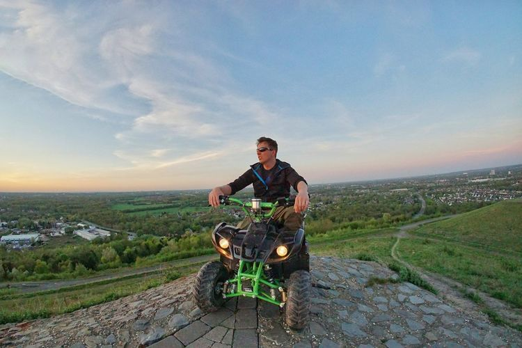 Man looking at view while riding quadbike on landscape against sky during sunset