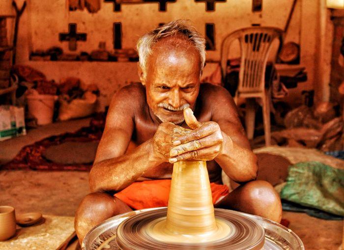 Shirtless senior man making pottery in workshop