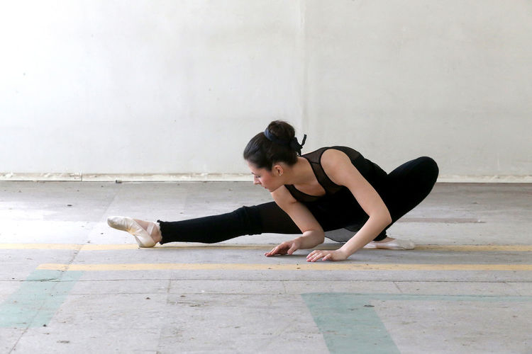 Full length of young woman doing ballet dance on floor