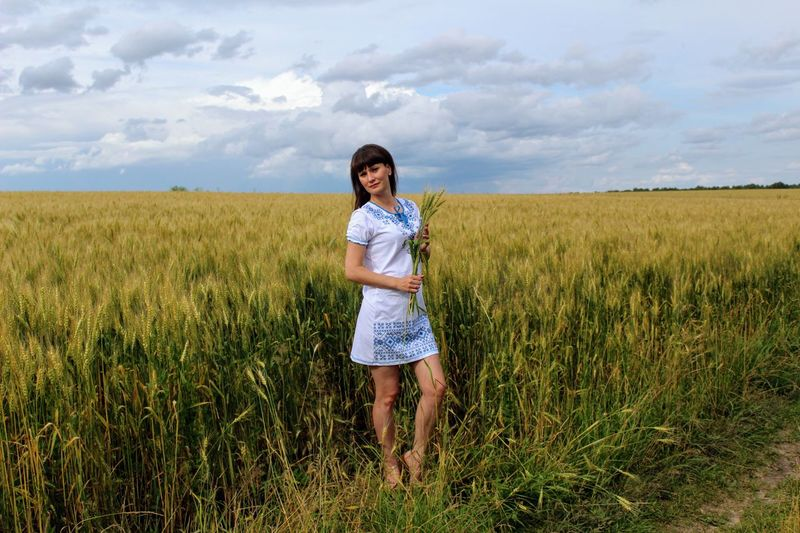 Portrait of young woman standing on landscape against cloudy sky
