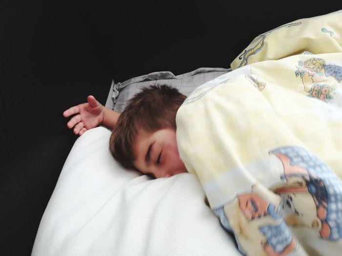 Cute boy sleeping on bed