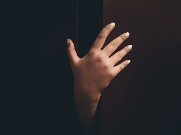 Close-up of woman hand on wall in darkroom