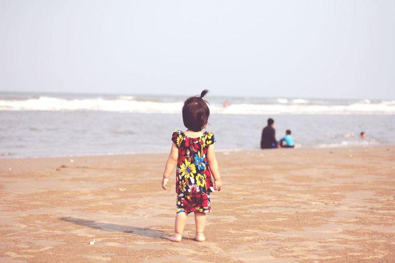 Rear view of little girl walking on beach against clear sky