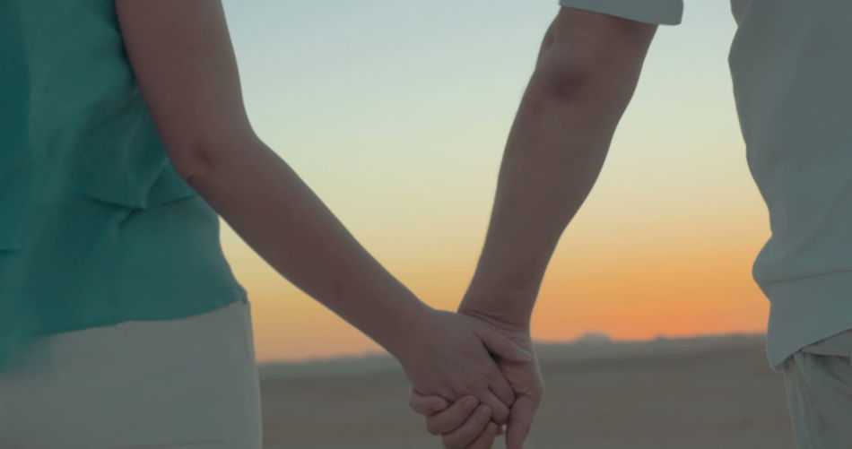 Midsection of man and woman standing against sky during sunset