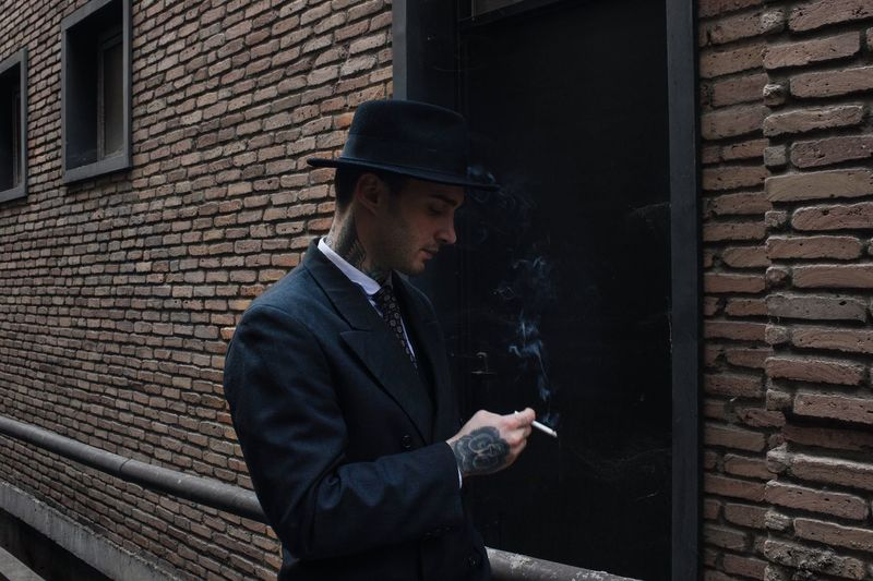 Man smoking cigarette against brick wall