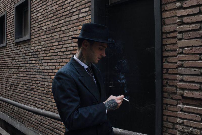 Man Smoking Cigarette Against Brick Wall