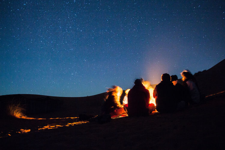 People Enjoying Campfire In Desert At Night