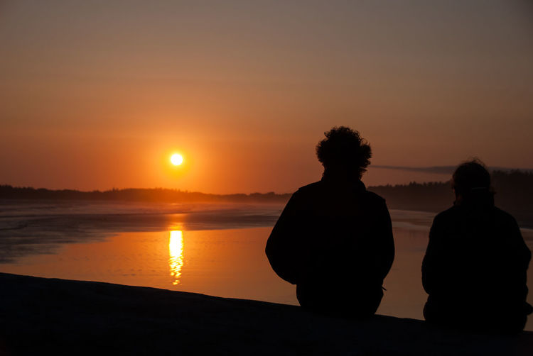 Silhouette couple sitting on shore against orange sunset sky