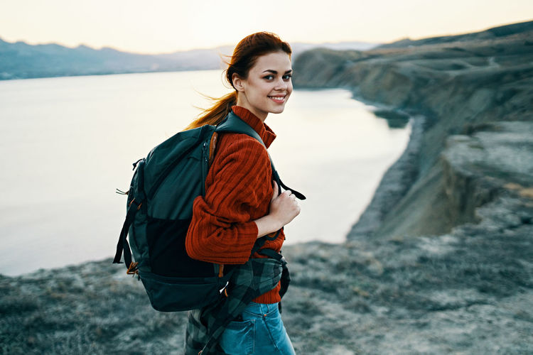 Side view of smiling young woman standing at shore