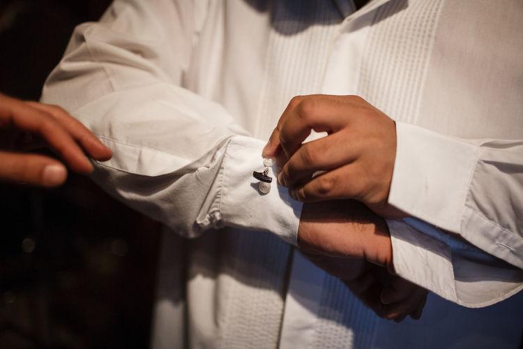 Midsection of groom adjusting cufflinks