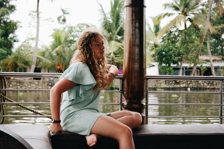Young woman sitting on railing against lake