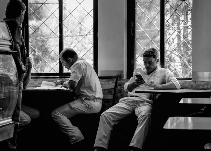 Blackandwhite Black & White Toboggan Sitting Men Indoors  Window Males  Table Adult Real People Casual Clothing People Group Of People Three Quarter Length Lifestyles Togetherness Transparent Mid Adult Men Mature Adult Day Have A Break