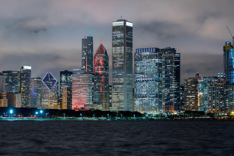Sea by illuminated buildings against sky