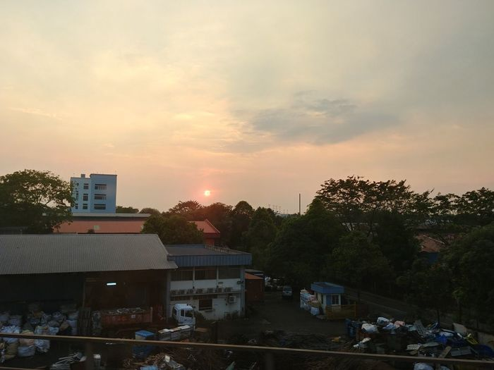 High angle view of trees and buildings against sky during sunset