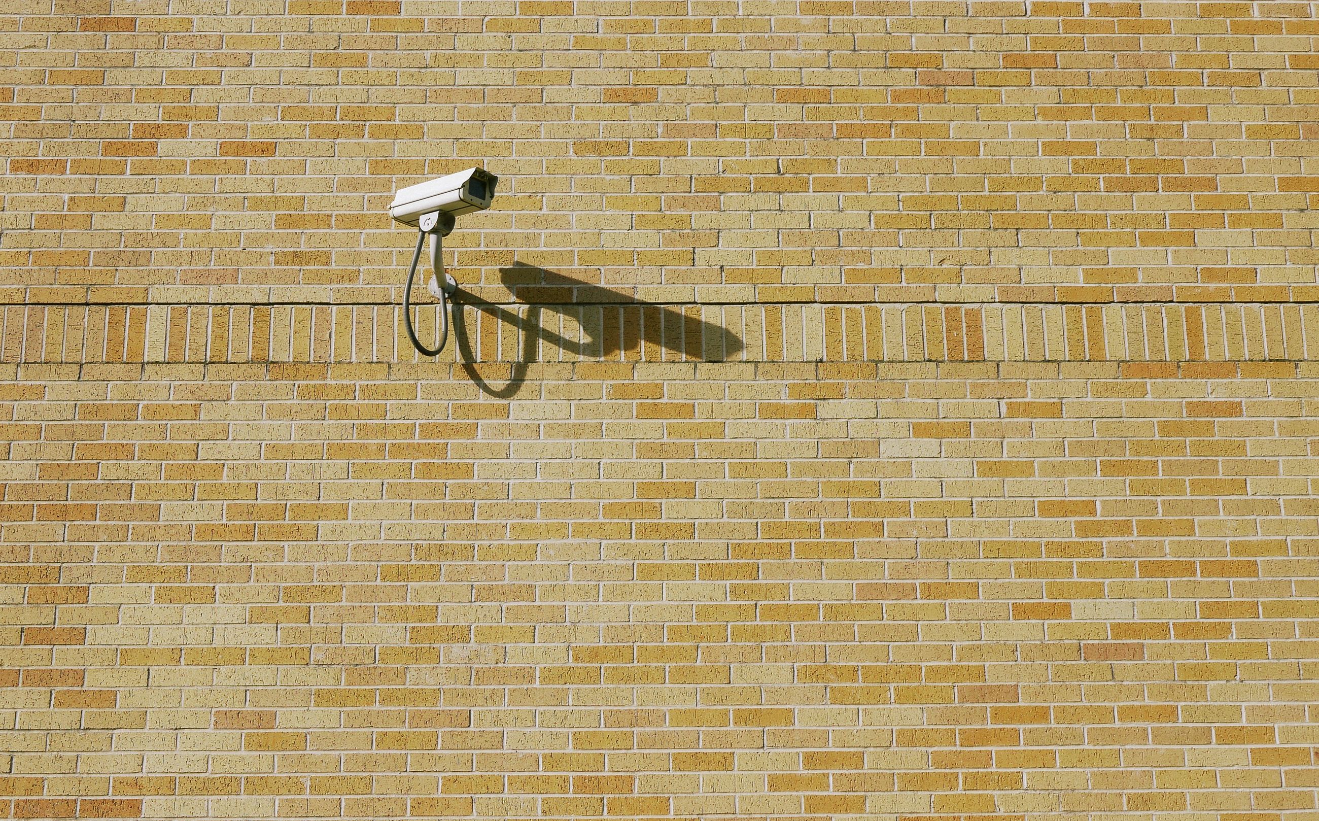 wall - building feature, tile, architecture, built structure, wall, brick, flooring, pattern, brick wall, no people, day, shadow, security camera, surveillance, outdoors, sunlight, building exterior, electricity, tiled floor, nature