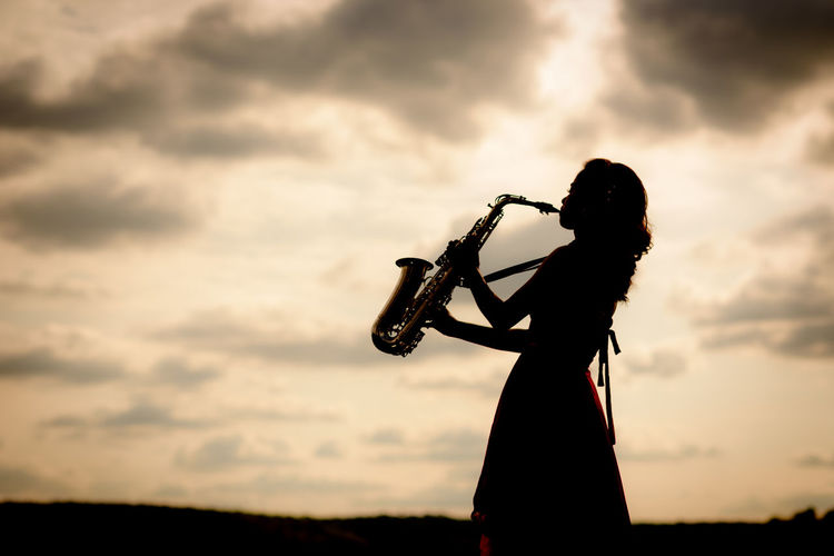 Side View Of Woman Playing Saxophone Against Cloudy Sky During Sunset