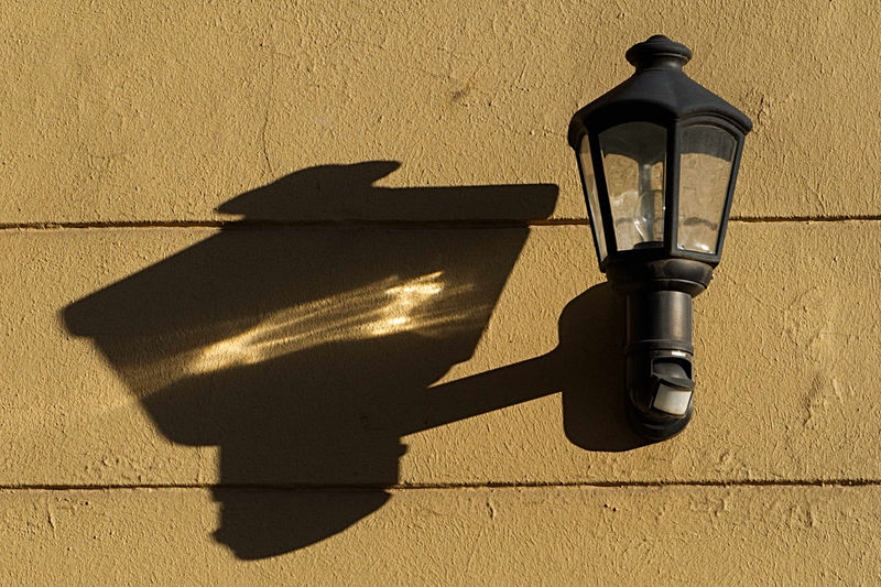 Street lamp with shadow on wall during sunny day