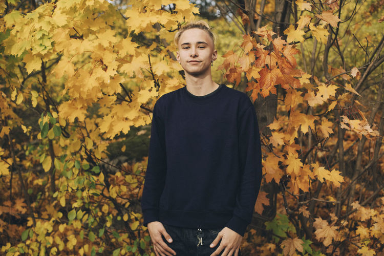 Portrait of young man standing on autumn leaves