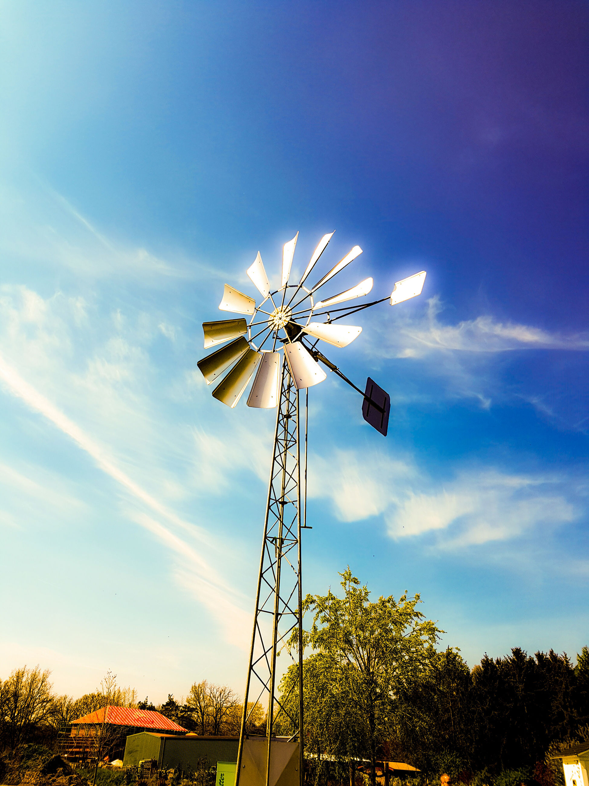 wind power, windmill, alternative energy, environmental conservation, low angle view, wind turbine, renewable energy, fuel and power generation, sky, traditional windmill, technology, cloud - sky, tree, field, cloud, rural scene, amusement park, water pump, blue, cloudy