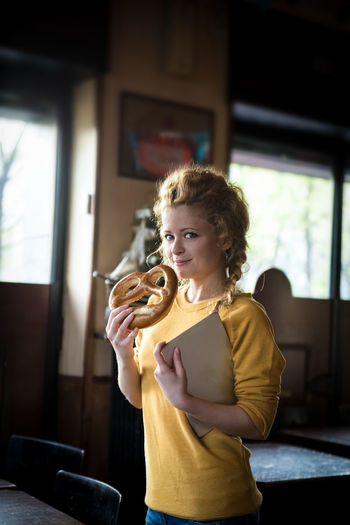 Portrait of smiling woman holding pretzel and tablet at cafe