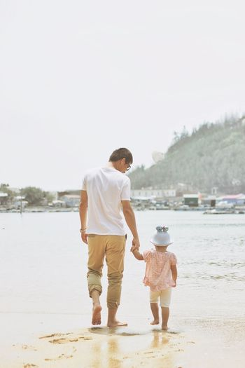 Rear View Of Father And Daughter Walking At Beach
