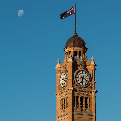 Low angle view of british flag on clock tower against blue sky