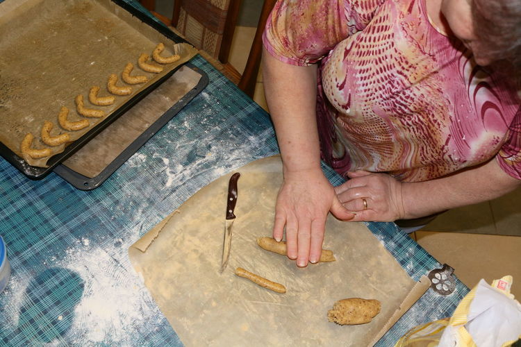 High angle view of senior woman preparing kipfel cookies in kitchen