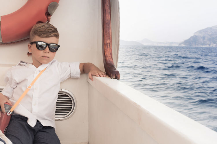 Boy wearing sunglasses while sitting in boat over sea