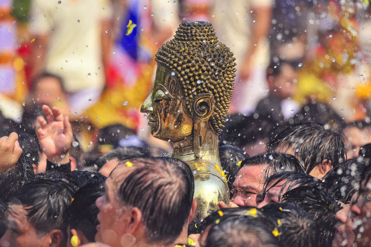 People carrying buddha statue during traditional ceremony
