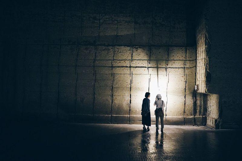 Two people walking in the dark
