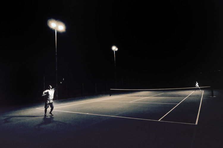 Court Floodlight Full Length Healthy Lifestyle Illuminated Lighting Equipment Night Only Men Outdoors People Professional Sport Real People Sport Sports Clothing Sportsman Tennis Tennis Tennis Ball Tennis Racket