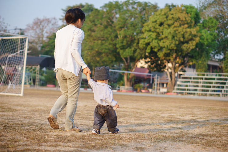 Rear view full length of woman walking with son on soccer field