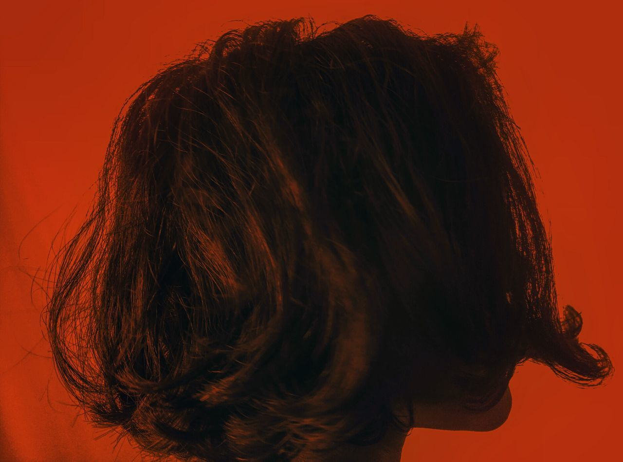 Close-up of woman against orange background