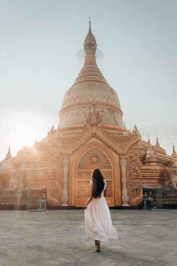Rear view of woman looking at temple against sky
