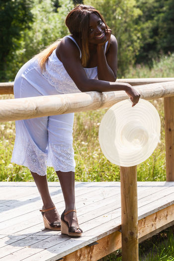 Young dark-skinned overweight woman with sunhat leans over a wooden railing Happiness Adult Casual Clothing Day Front View Full Length Hairstyle Holding Leisure Activity Lifestyles Nature One Person Outdoors Park People Portrait Real People Relaxtion Standing Summer Sunlight Women Wood - Material Young Adult Young Women