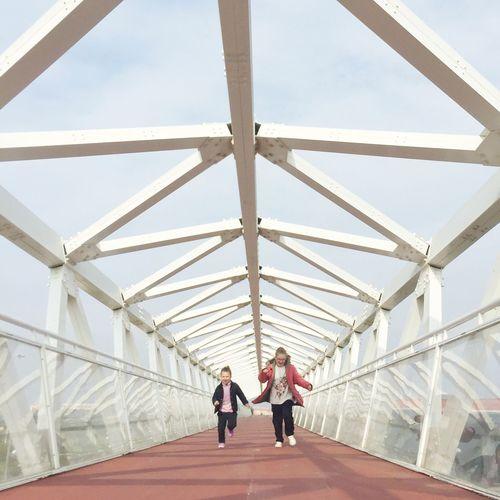 Siblings running on covered bridge