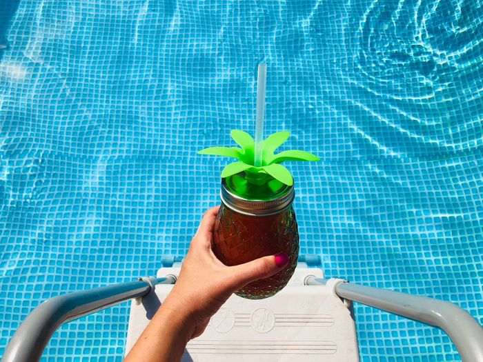 Midsection of person holding plant by swimming pool