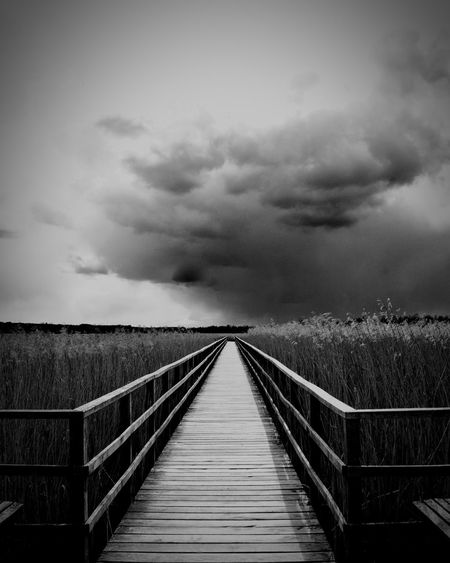 Empty boardwalk amidst field against cloudy sky