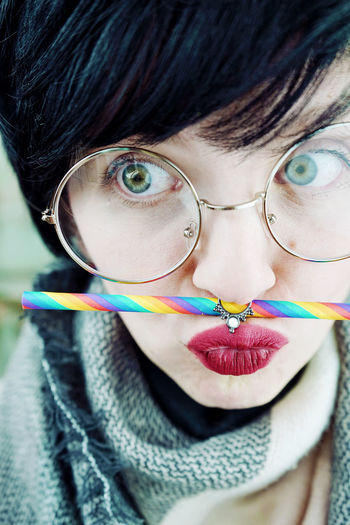 Close-Up Of Hipster Woman Wearing Eyeglasses With Colorful Drinking Straw