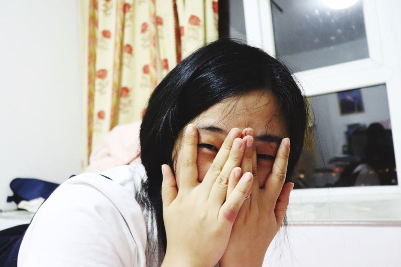 Close-Up Portrait Of Young Woman Covering Face At Home