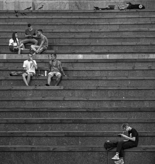 People relaxing on staircase in city
