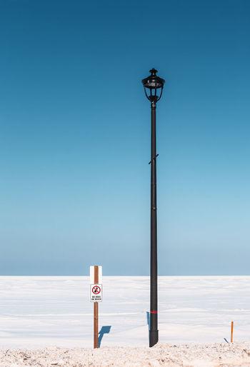 Street light on beach against clear blue sky