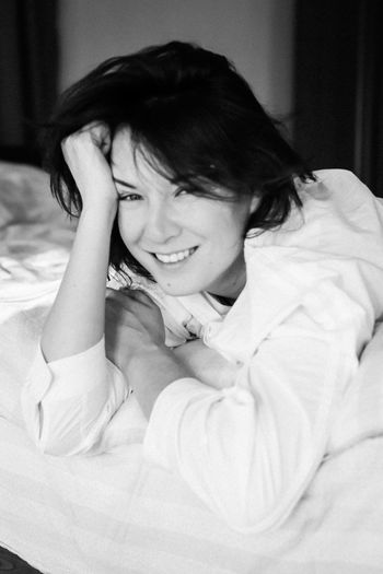 Portrait of smiling woman lying on bed at home